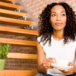woman sitting on steps with coffee cup