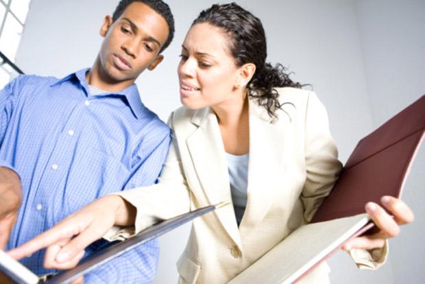 woman looking at man's portfolio