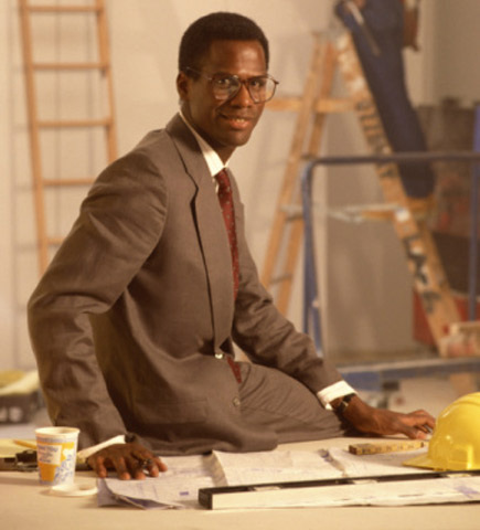 African american electrical engineer sitting on desk at work site