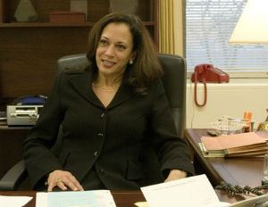 kamala harris smiling at desk