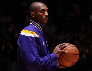 Photo of Kobe Bryant in a Lakers jacket holding a basketball