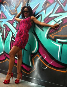 Amber Cuff posing against a graffitied wall in London