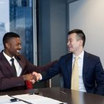 Ray J and Ray Lee of Cowboy Wholesale shake hands after signing the paperwork cementing their $31 million Raycon distribution deal. (Image: Raycon)