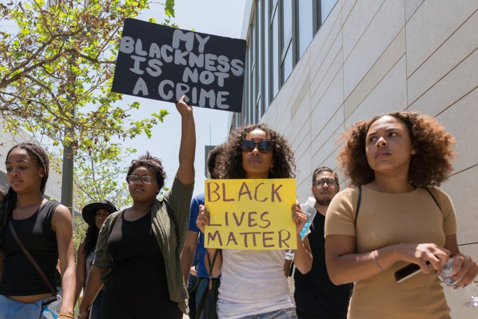 Black lives matter protestors holding a poster during march