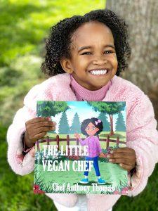 Ashlyn holding the Little Vegan Cookbook