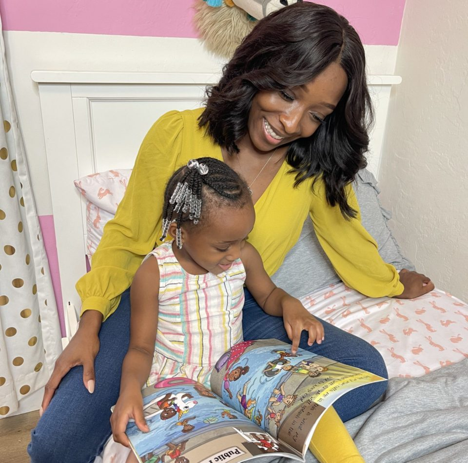 Author and professor, Dr. Rokeshia Renné Ashley enjoys reading her new children's book SunFlower Child with daughter Emery.